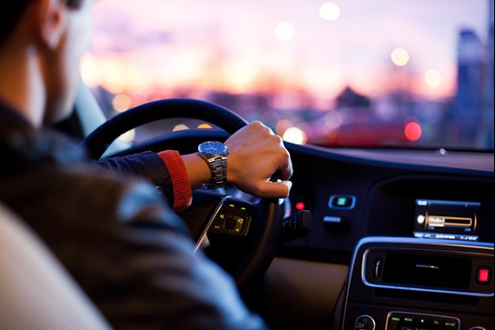 Auto Insurance 101. A driver sits in the evening traffic with his hand resting on the steering wheel.